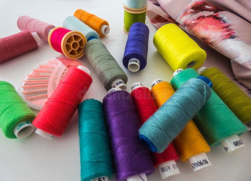 Spoelen met gekleurde katoenen draden voor het naaien, naaiende toebehoren, geplaatste naalden stock fotografie