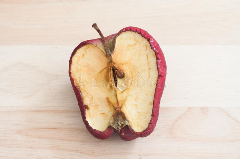 Spoiled bad red apple on wooden background stock photography