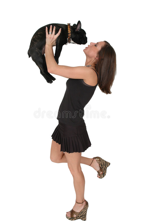 Spoiled Bull Dog. Beautiful fashionable woman with her French Bull dog. Woman holding her puppy bull dog over her head with a kissy face royalty free stock photography