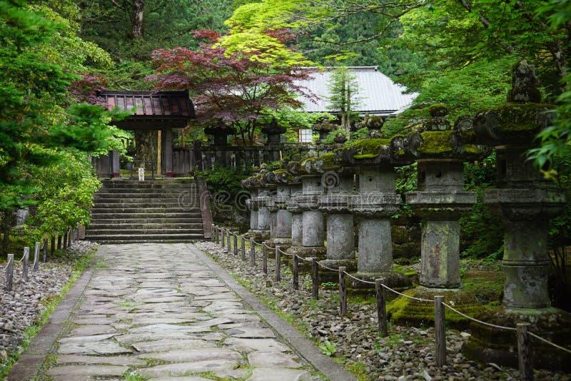 Spokój i pokojowy zielony japończyka ogród z małymi kamienistymi statuami, krokami i świątynią jako symbol, harmonia, równowaga i obrazy stock