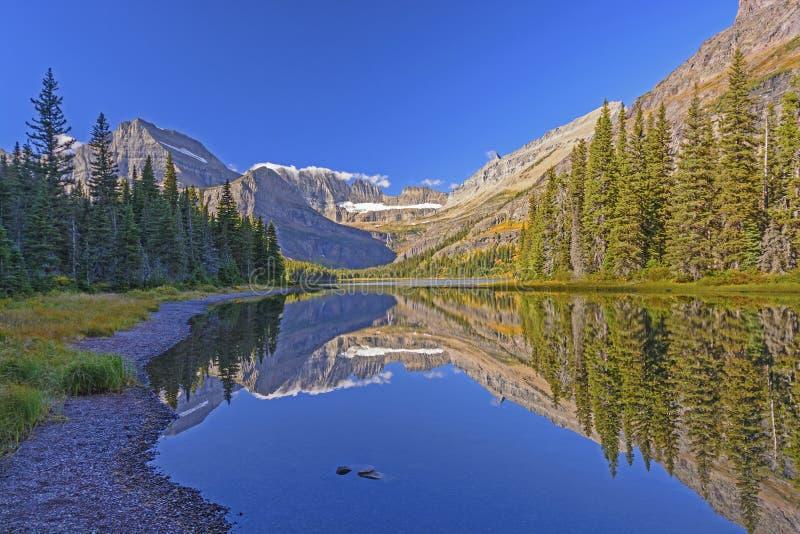Spokój wody w ranku na Alpejskim jeziorze w spadku fotografia stock