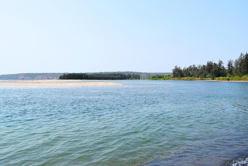 Spokojna artykuły plaża z Czystą błękitne wody, drzewami i wyspą, fotografia stock