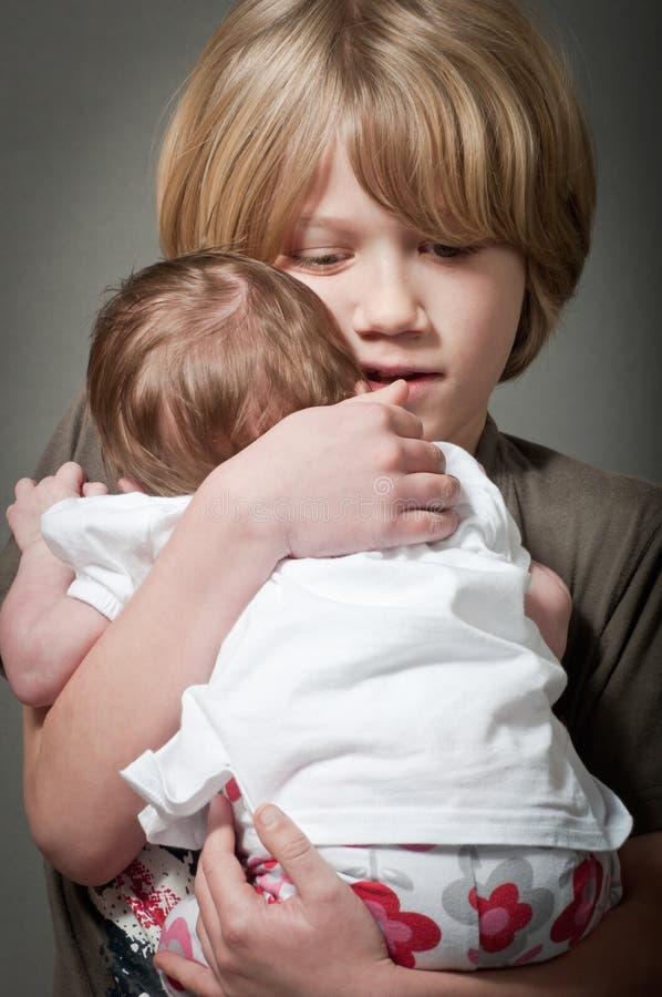 Spokojna chłopiec trzyma nowonarodzonego dziecka fotografia stock