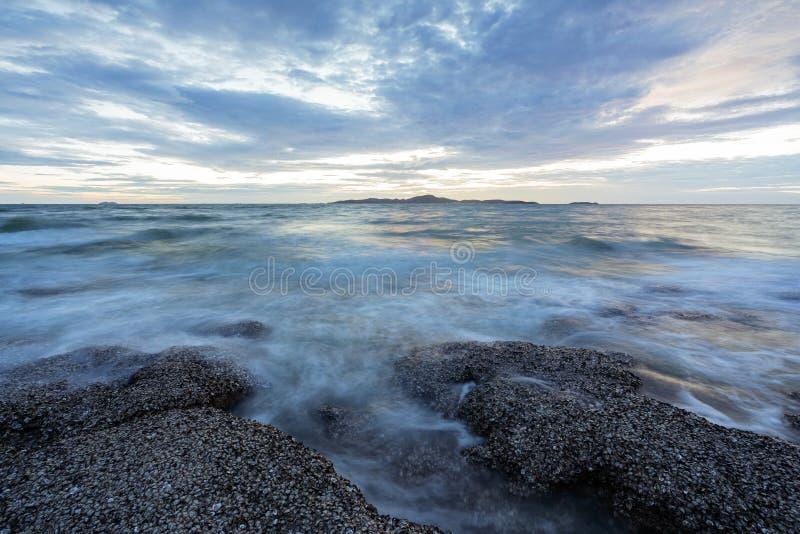 Spokojna kamienista zatoka po zmierzchu Wolna ?aluzi pr?dko?? dla g?adkiego pozioma wody i marzycielskiego skutka zdjęcia stock
