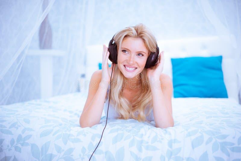 Spokojna kobieta cieszy się niektóre muzykę w jej sypialni zdjęcia stock