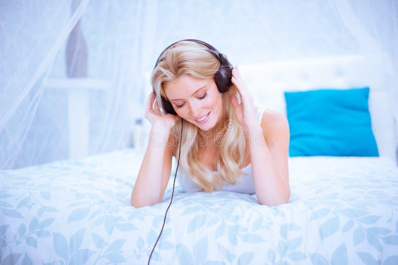 Spokojna kobieta cieszy się niektóre muzykę w jej sypialni zdjęcie stock