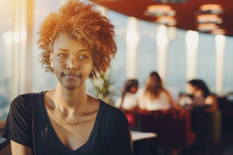 Spokojna młoda kędzierzawa czarna dziewczyna w biurowej kawiarni zdjęcie royalty free