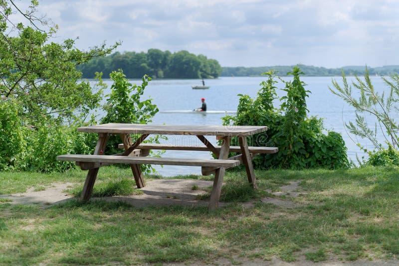 Spokojna scena drewniany stół z dwa ławkami przy jeziora wybrzeżem obrazy stock