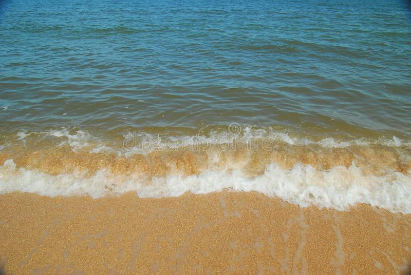 Spokojnego morza kipiel przy skorupa piaska plażą T?o fotografia stock