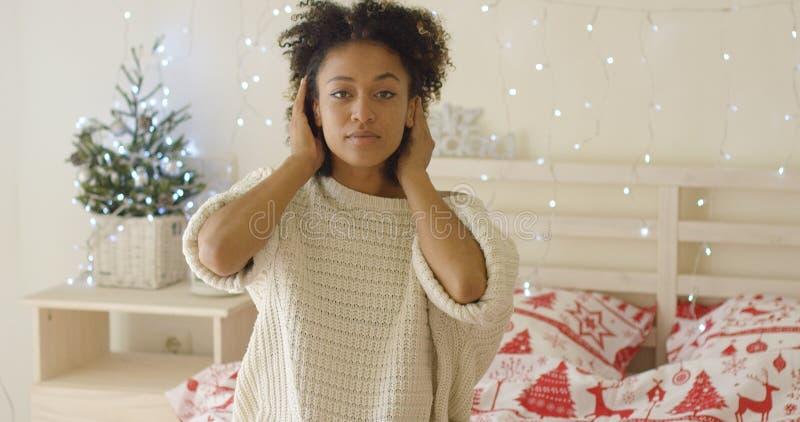 Spokojnej młodej kobiety adusting włosy w łóżku fotografia royalty free