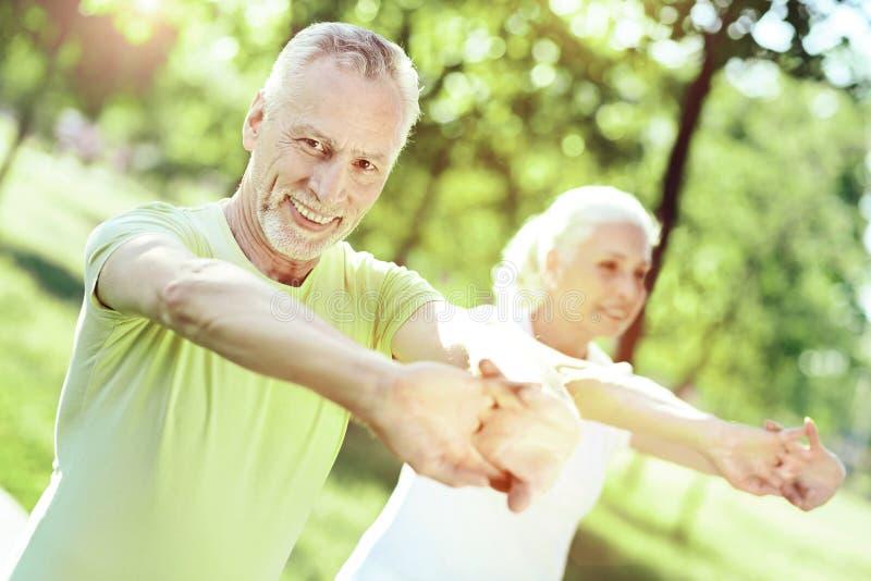 Spokojny aktywny emeryt ono uśmiecha się podczas gdy ćwiczący zdjęcie stock