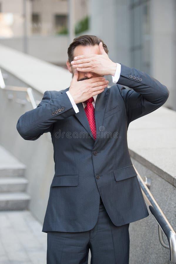 Spokojny biznesmen z rękami zakrywa jego oczy i usta zdjęcie royalty free