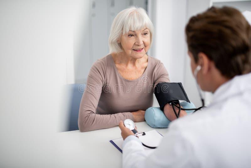 Spokojny damy ono uśmiecha się i doktorski mierzący jej ciśnienie krwi fotografia stock