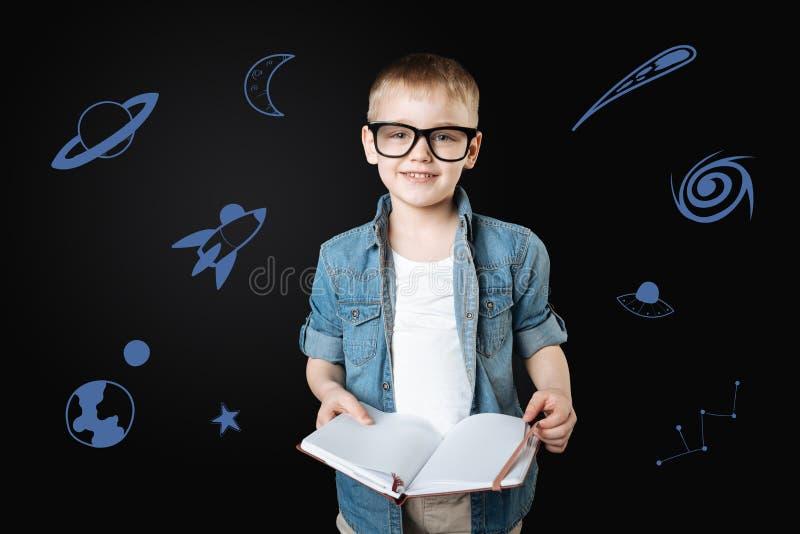 Spokojny dziecko trzyma książkę i marzy o przestrzeni obrazy stock