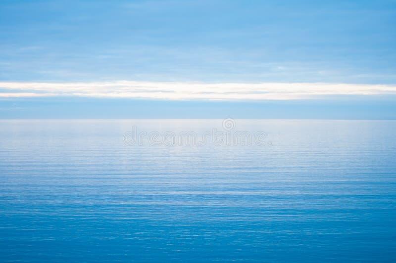 Spokojny i otwarte morze zamazuje w niebieskie niebo wciąż zdjęcie royalty free