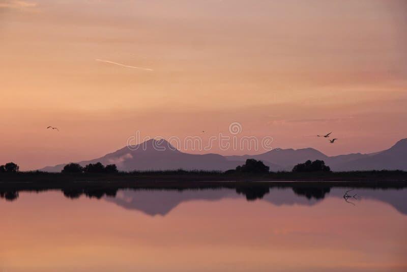 Spokojny jezioro z górami przy zmierzchem obrazy stock