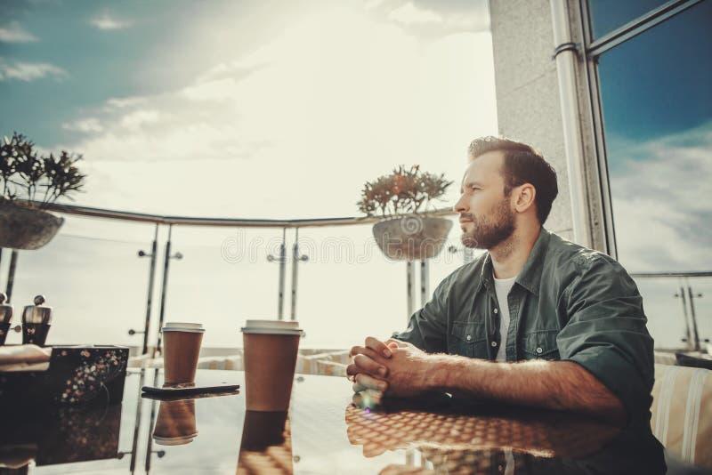 Spokojny mężczyzna obsiadanie przy stołem z filiżankami kawy zdjęcia royalty free