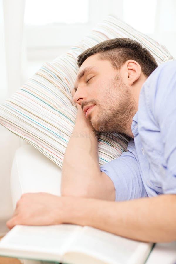 Spokojny młodego człowieka lying on the beach na kanapie z książką w domu obrazy stock