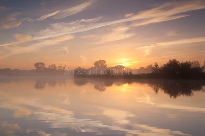 Spokojny mglisty wschód słońca nad dzikim jeziorem obrazy stock