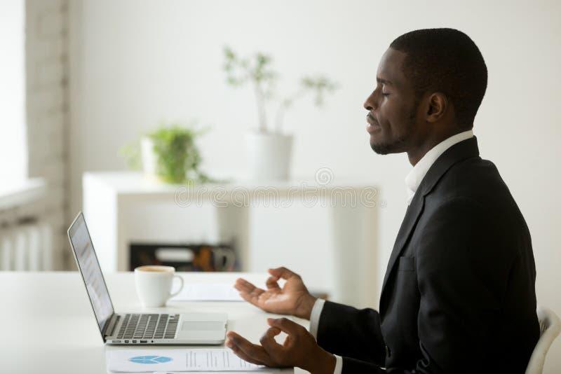 Spokojny pokojowy afroamerykański biznesmen w kostiumu medytuje przy obrazy stock
