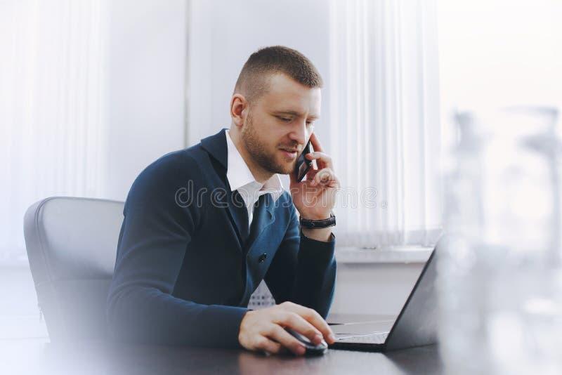 Spokojny poważny młody człowiek używa telefon przy stołem w biurze podczas gdy pracujący obraz royalty free