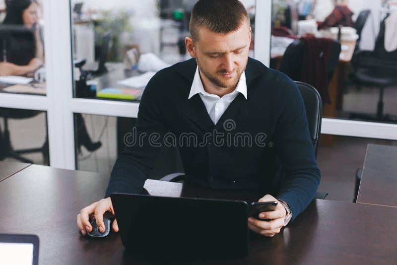 Spokojny poważny młody człowiek używa telefon przy stołem w biurze podczas gdy pracujący zdjęcia royalty free