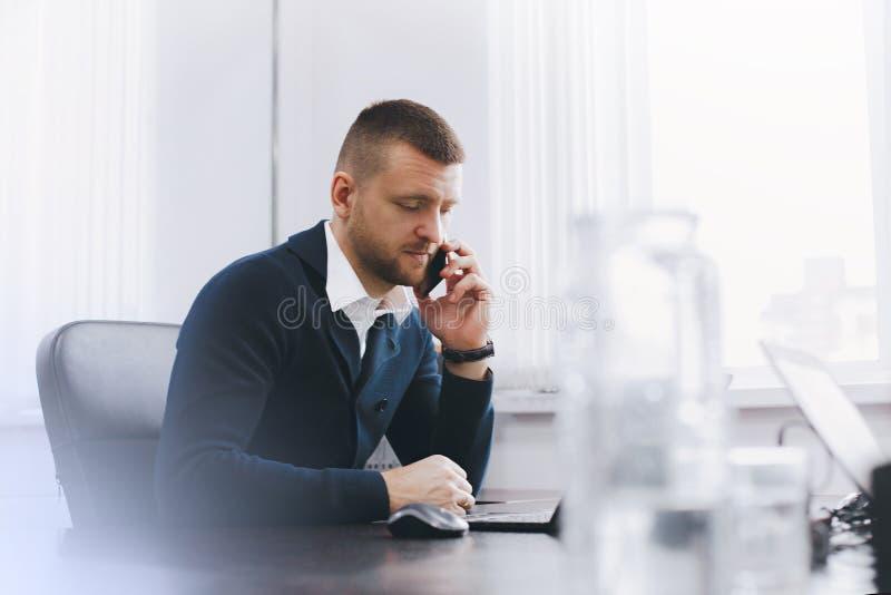 Spokojny poważny młody człowiek używa telefon przy stołem w biurze podczas gdy pracujący fotografia stock