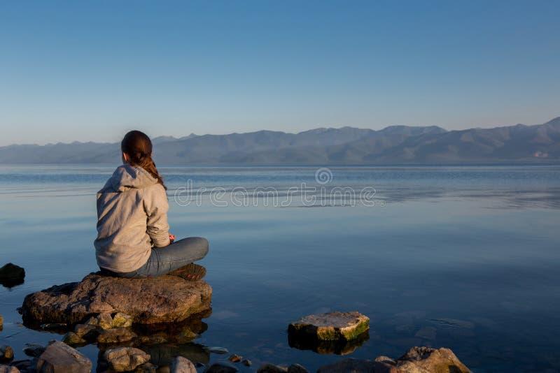 Spokojny zmierzch nad rzeką Dziewczyna siedzi na dużym kamieniu, lato spokojny wieczór fotografia royalty free