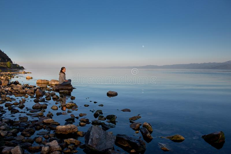Spokojny zmierzch nad rzek? Dziewczyna siedzi na du?ym kamieniu Lato spokojny wiecz?r, ksi??yc w pe?ni obrazy royalty free