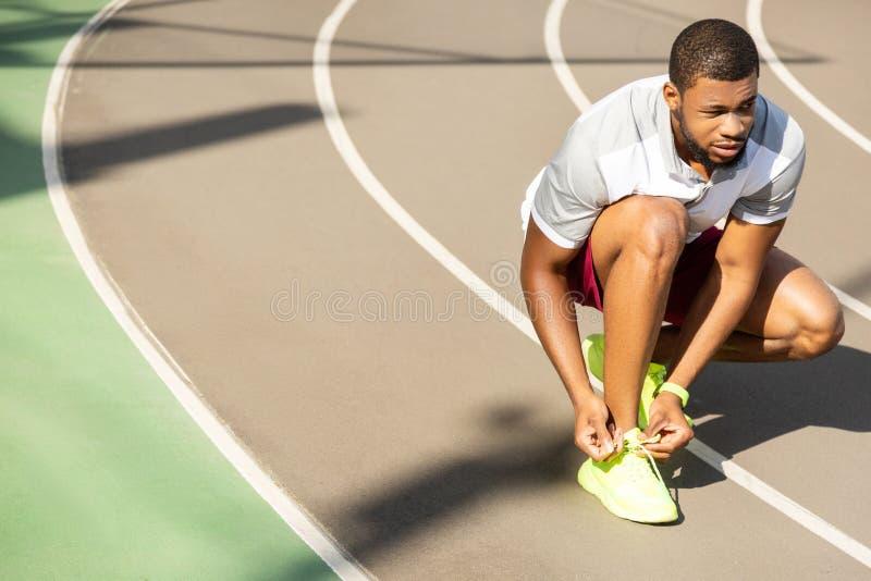 Spokoju dysponowanego amerykanin afrykańskiego pochodzenia męski biegacz wiąże koronki fotografia stock