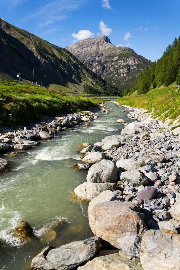 Spol River flowing in Lake Livigno, Corno Brusadella Mountain background. Spol River flowing in Lake Livigno with Corno Brusadella Mountain in background, Italy royalty free stock images