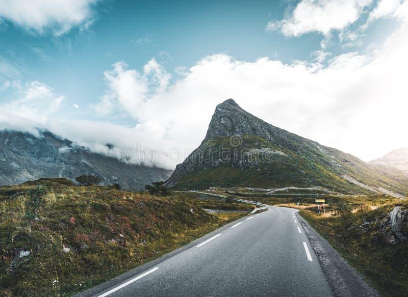 Spolningsvägtur in mot berget i Reine på Lofoten öar med berg i bakgrunden Molnig och lynnig himmel fotografering för bildbyråer