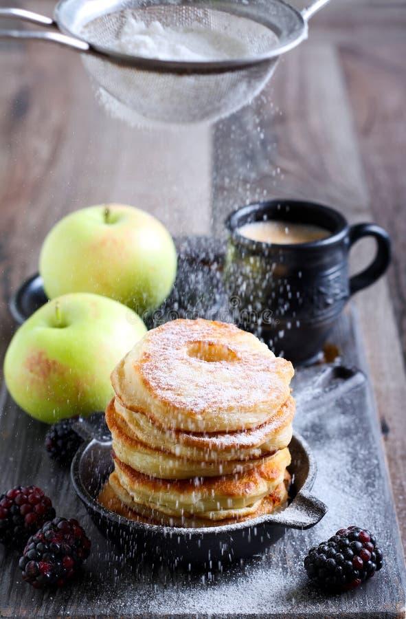 Spolverando con lo zucchero a velo sopra le frittelle di mela fotografia stock libera da diritti