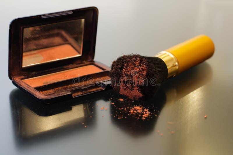 Spolverizzi la spazzola e una scatola di rossetto con uno specchio fotografia stock libera da diritti