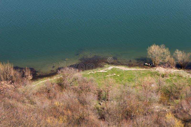 Sponda del fiume con la barca nel tempo di primavera dalla cima di scolarsi fotografia stock