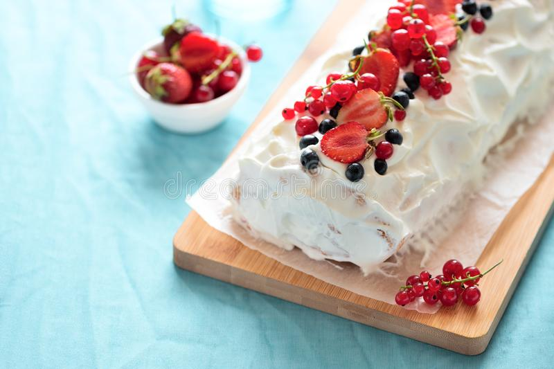Sponge biscuit cake roll filling whipped cream and berries decorated strawberry, blueberry and red currants on turquoise stock image