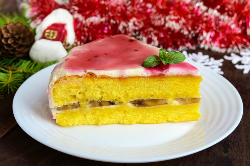 Sponge cake with a layer of banana, milk cream and cranberry syrup stock photography