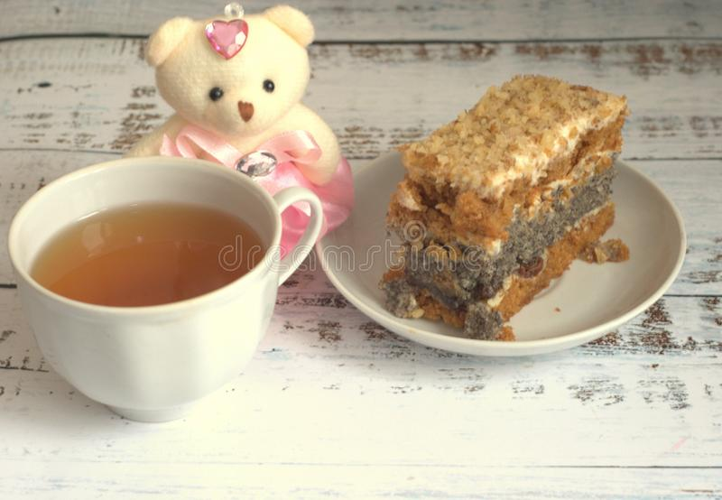 Sponge cake with poppy seeds on a plate, a cup of tea and a teddy bear lying on a wooden table royalty free stock photos