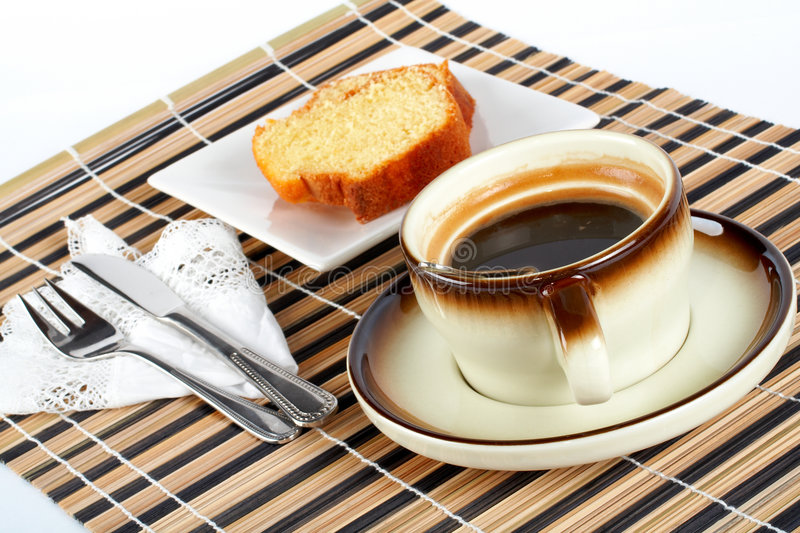 Sponge cake with the spoon inside cup of coffee, knife and fork stock photo