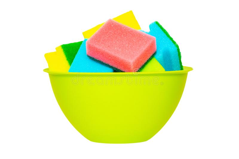 Sponge isolated. Close-up of green plastic bowl with various colorful sponges or scouring pads in it isolated on white background. Household chore concept stock image