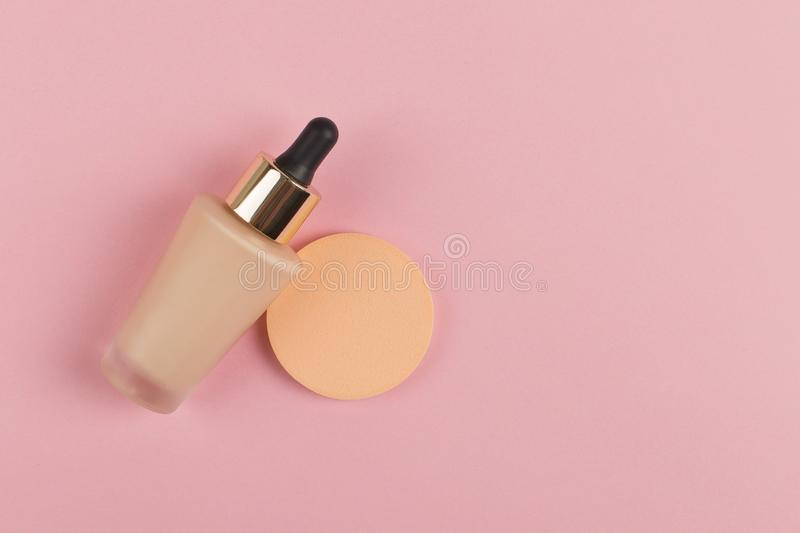 Sponges, a beautiful blender for applying foundation or powder and a bottle of concealer. Flat lay on a pink background, copy. Sponges, a beautiful blender for royalty free stock images