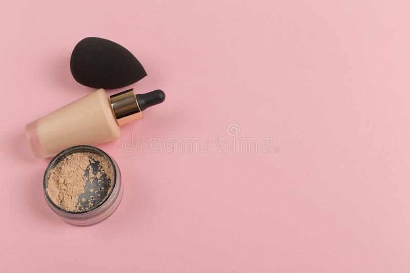 Sponges, a beautiful blender for applying foundation or powder and a bottle of concealer. Flat lay on a pink background, copy. Sponges, a beautiful blender for royalty free stock photography