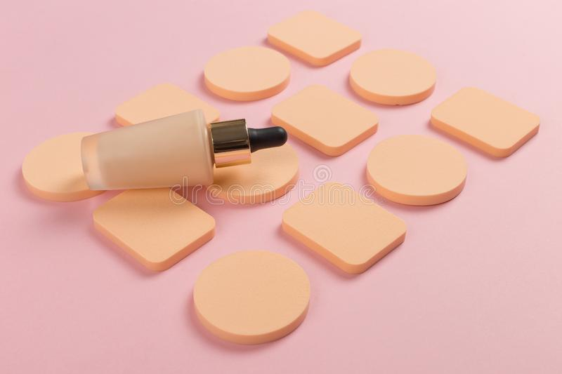 Sponges, a beautiful blender for applying foundation or powder and a bottle of concealer. Flat lay on a pink background, copy. Sponges, a beautiful blender for royalty free stock photo