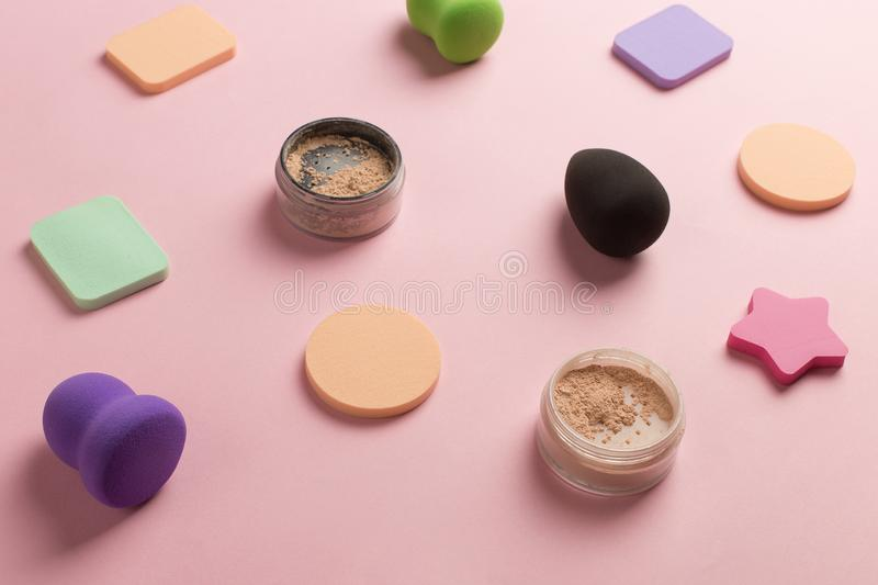 Sponges, beauty blender for applying foundation or powder. Flat lay on a pink background, copy space. Set, many, tonal, highlighting, object, bottle, liquid stock photography