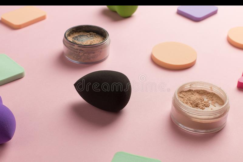 Sponges, beauty blender for applying foundation or powder. Flat lay on a pink background, copy space. Set, many, tonal, highlighting, object, bottle, liquid stock photo