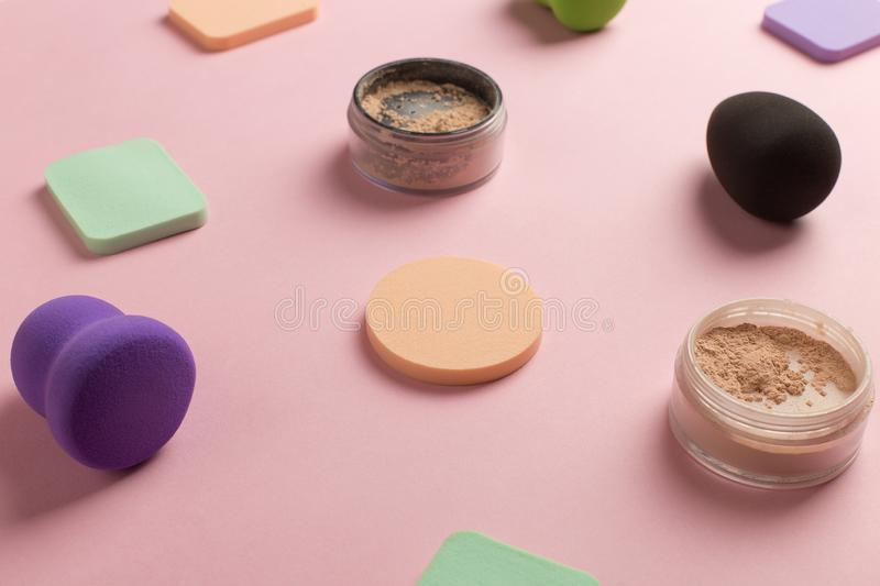 Sponges, beauty blender for applying foundation or powder. Flat lay on a pink background, copy space. Set, many, tonal, highlighting, object, bottle, liquid stock image