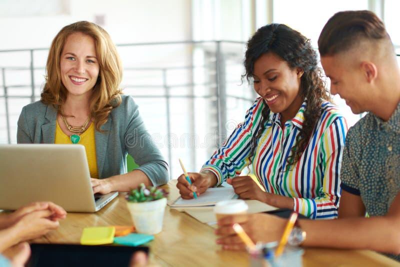 Spontaan beeld van een groep met succesvolle bedrijfsdiemensen in een geanimeerde brainstormingsvergadering worden gevangen royalty-vrije stock fotografie
