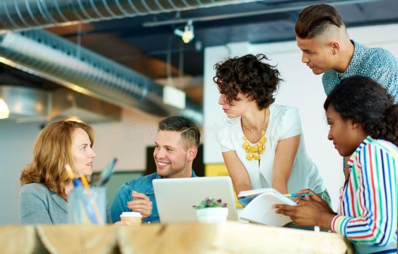 Spontaan beeld van een groep met succesvolle bedrijfsdiemensen in een geanimeerde brainstormingsvergadering worden gevangen royalty-vrije stock foto's