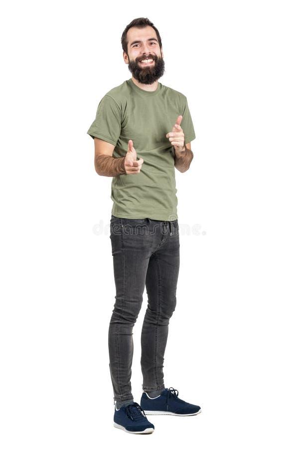 Spontaan lachende gebaarde mens die in groene t-shirt vingers richten op camera stock foto