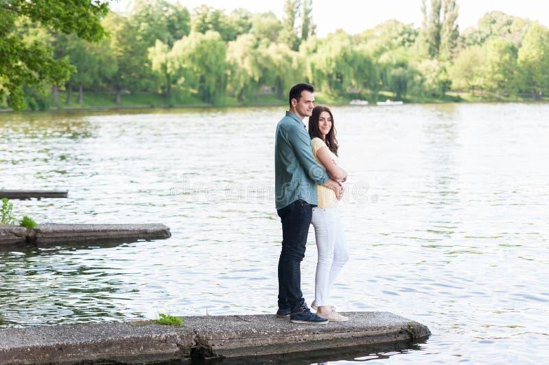 Spontaan paar in liefde, die op een steenpijler wordt omhelst royalty-vrije stock afbeelding